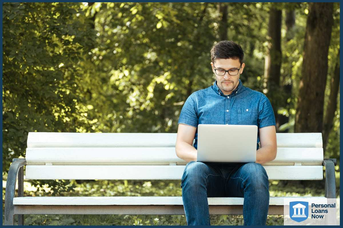 man on laptop in park